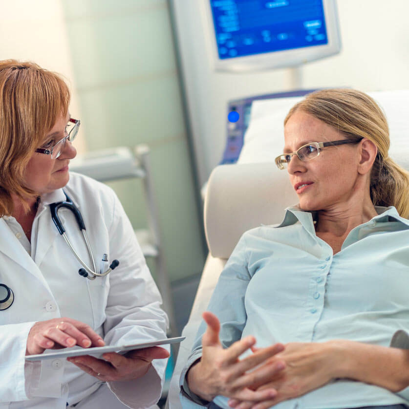 Doctor speaks with a female patient in an exam room