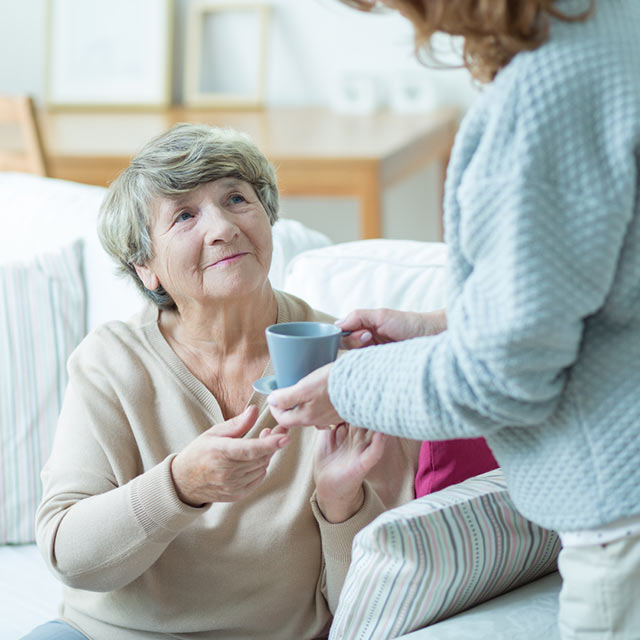 Caregiver handing woman a cup of coffee