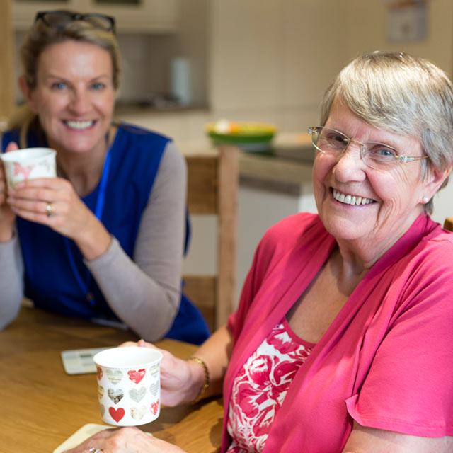 Older woman enjoying coffee with her daughter at the kitchen table
