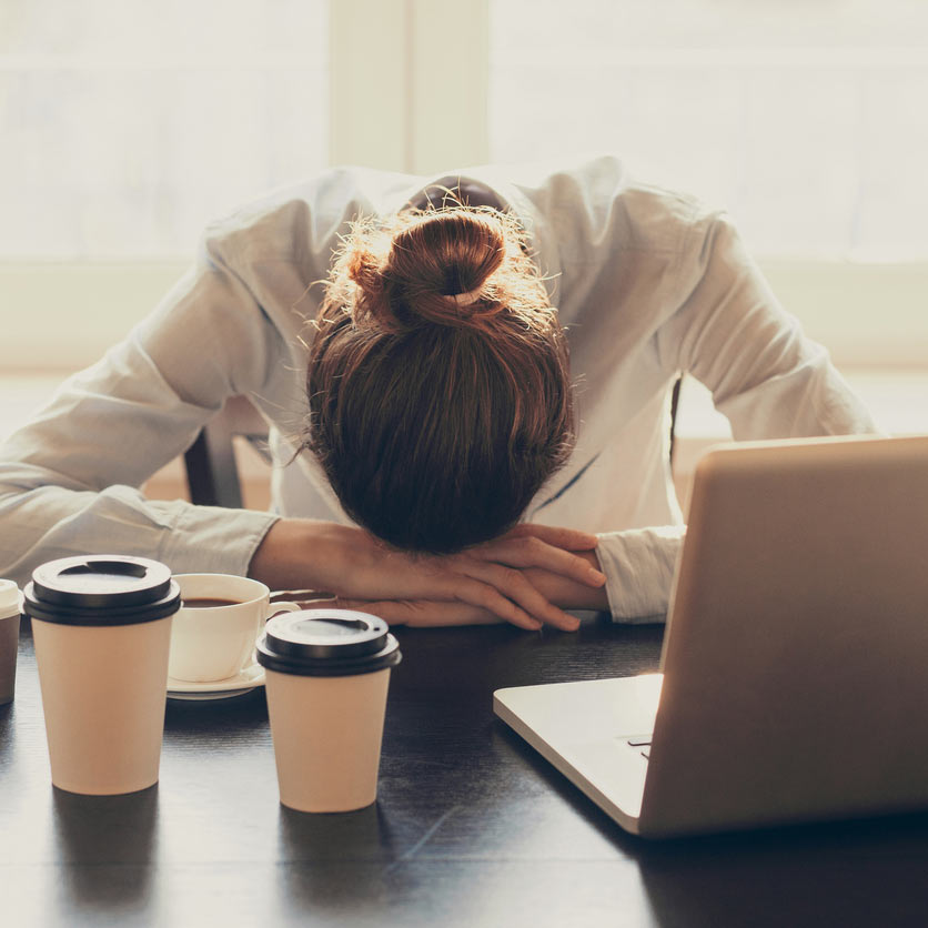Tired woman resting her head against her desk