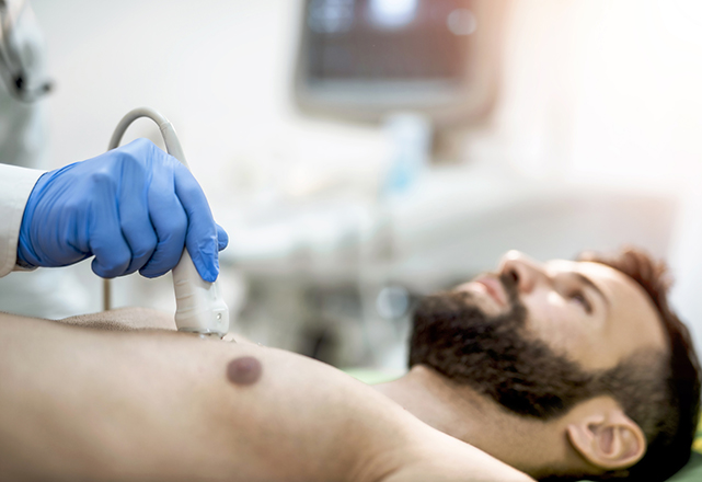 aortic disease - doctor performing ultrasound on man's chest