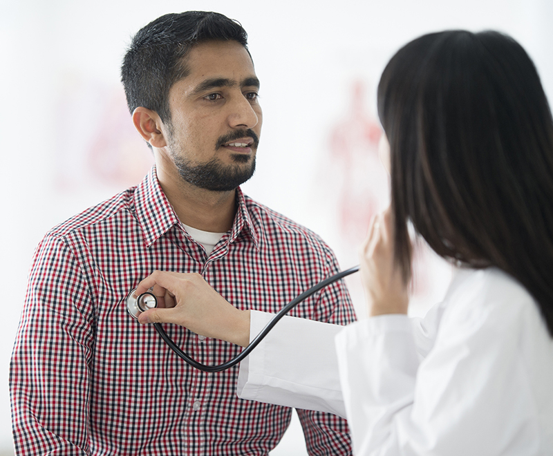 doctor listening to male patient's chest