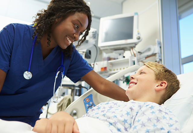 nurse checking on young boy in hospital bed