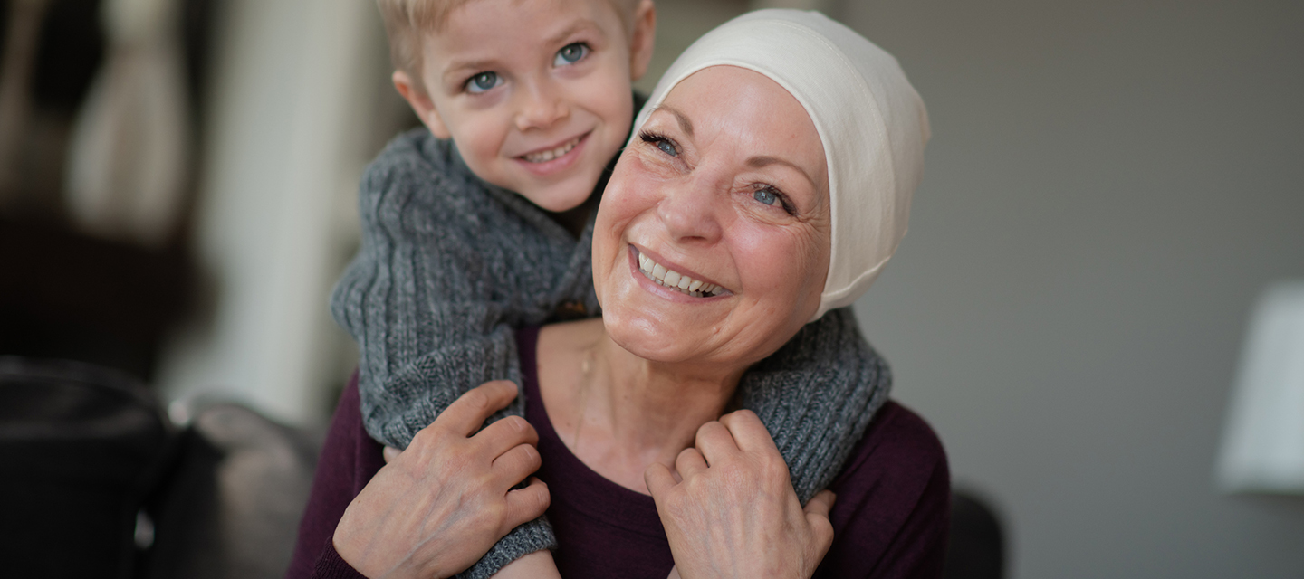 Grandmother with cancer smiling with grandson - cardio-oncology