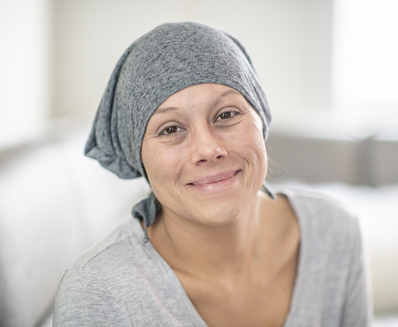 woman wearing scarf looking into camera - cardio-oncology