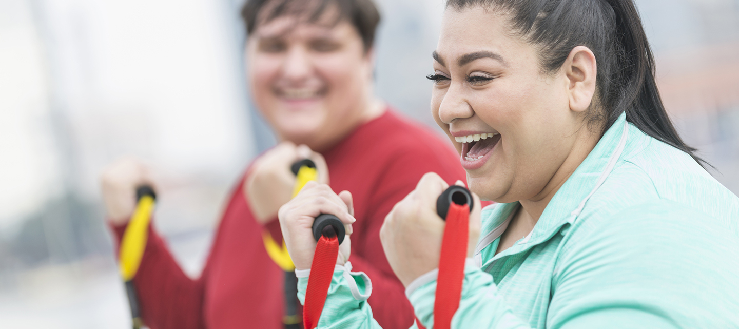 woman smiling while exercising with male in the background