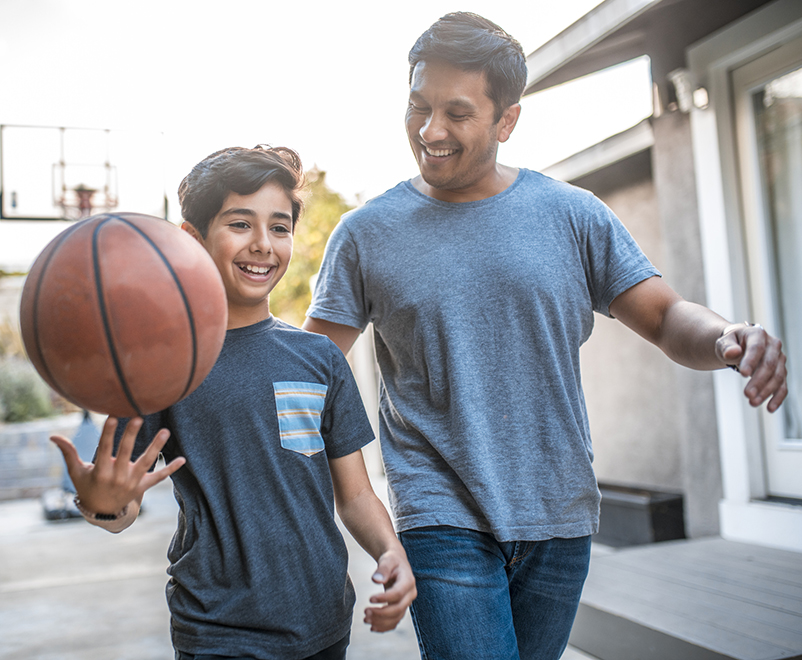 son holding basketball with father