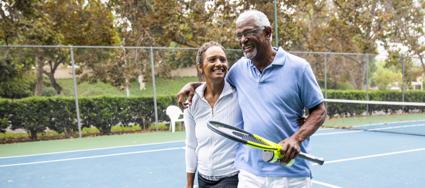 Mature couple walking in tennis court
