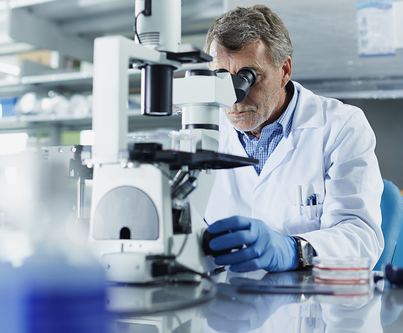 male scientist looking through microscope