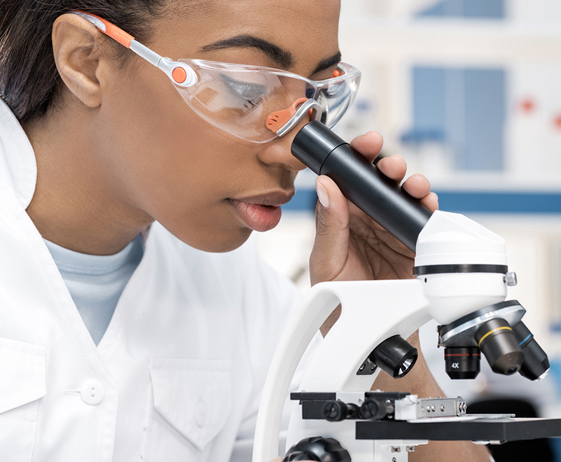 woman wearing goggles looking into microscope