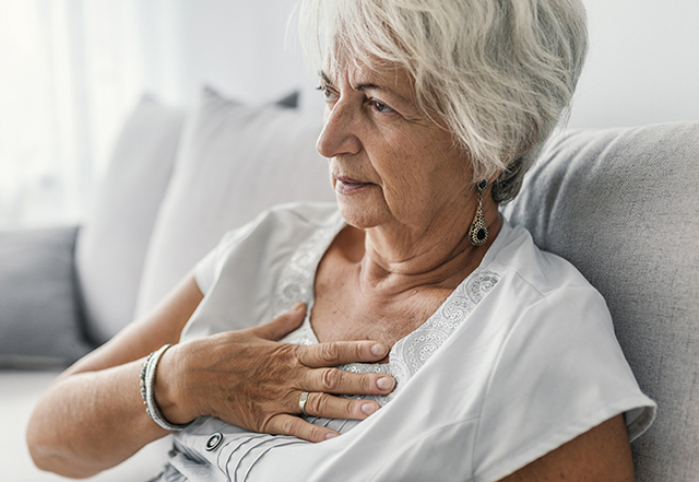 heart disease in women - mature woman holding chest in pain