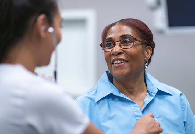 mature woman looking at nurse with stethoscope