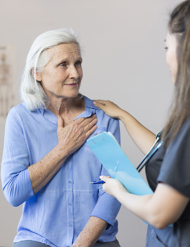 mature woman with hand on her chest with doctor