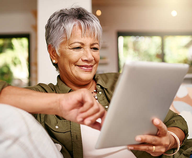 Mature woman using tablet on couch