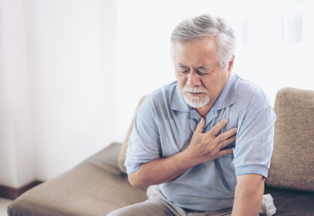 elderly man holding chest in pain - heart and vascular institute