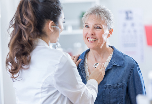 heart and vascular - doctor listening to mature woman's chest