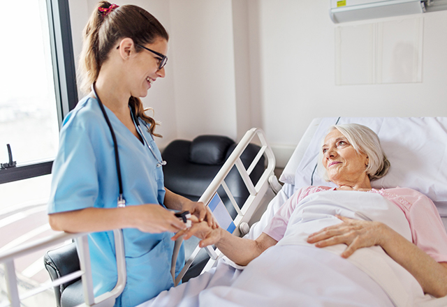 nurse adjusting oxymeter on mature female patient - heart and vascular institute