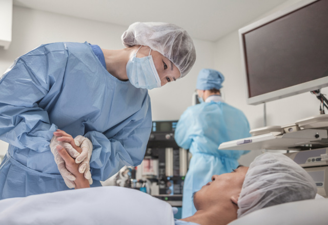 surgeon holding patient's hand - heart and vascular institute