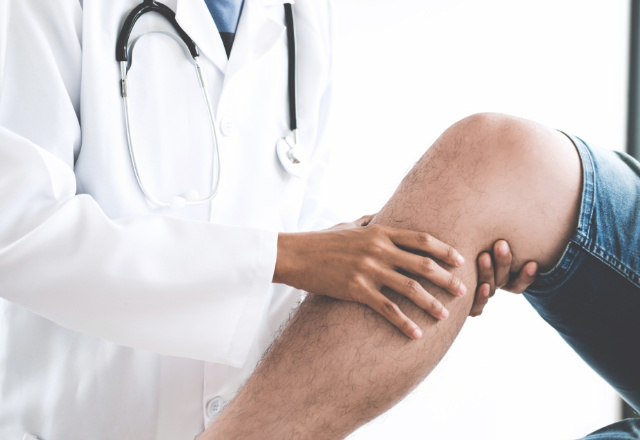 doctor examining patient's leg - heart and vascular institute