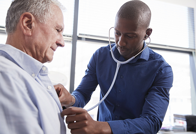 doctor listening to patient heart - heart and vascular institute
