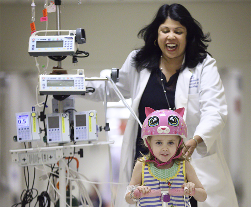Dr. Sapna Kudchadkar and a patient ride down the hall