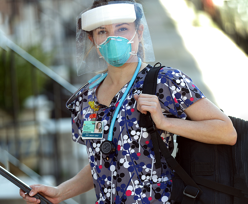 Amy Kilen walks into a patient's home while wearing PPE.