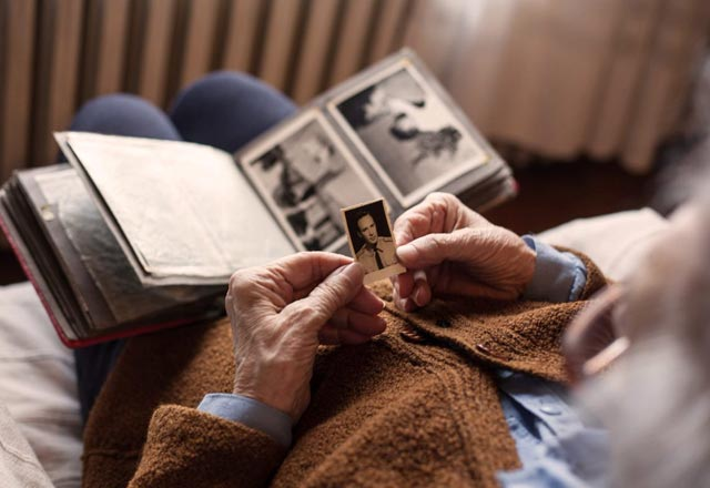 Elderly person looking at old photographs