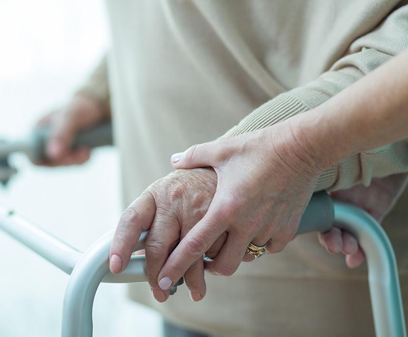 A caregiver helps an elderly patient use their walker.
