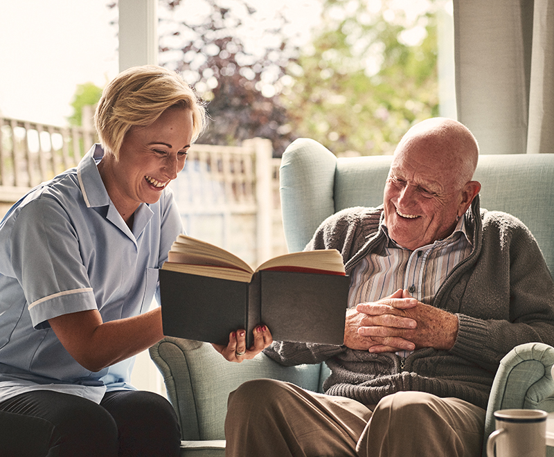 A caregiver reads a book with an elderly male patient in his home.