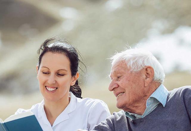 palliative care - nurse reading book with mature male patient