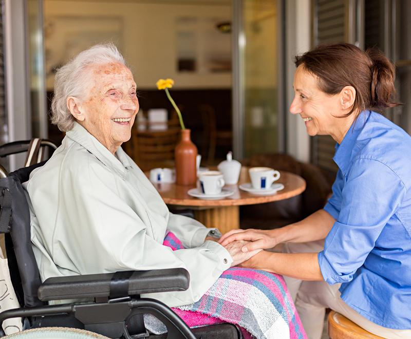An elderly woman and her adult daughter share laughter together while seated at a table.