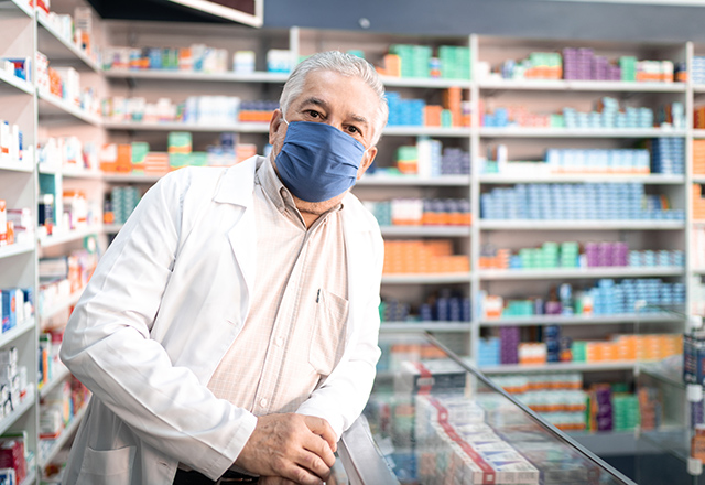 Pharmacist in pharmacy at computer