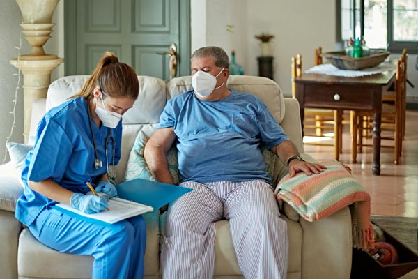 Physician sitting on couch with patient in home