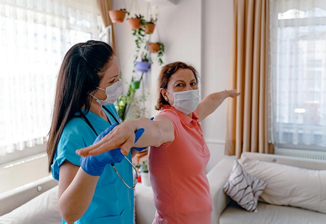 Physician working with patient in home on therapy techniques