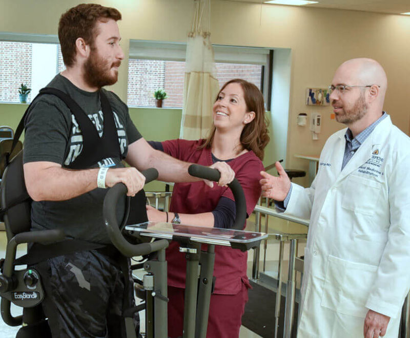 a therapist and physiatrist help a patient with physical therapy