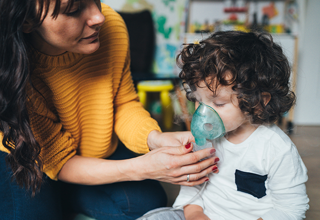 A woman adjusts a breathing treatment mask on a young child.