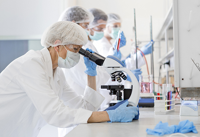 scientist looking at a microscope