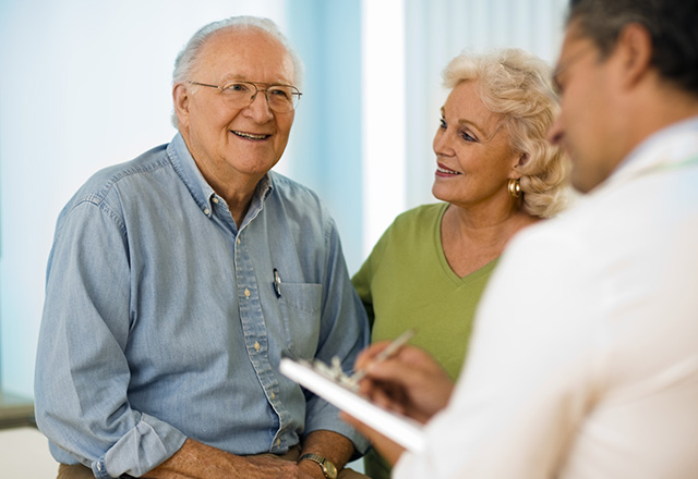 senior couple speaks to a doctor