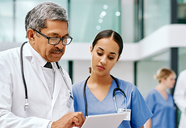a doctor and nurse review paperwork