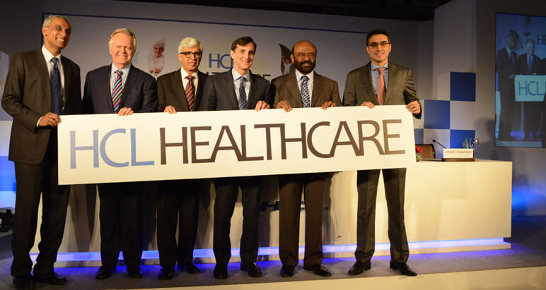 Executives holding up a HCL Healthcare sign.