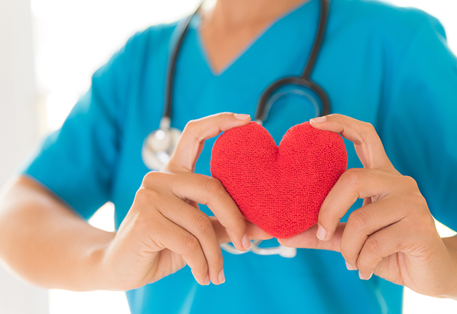A nurse holds up a felt heart