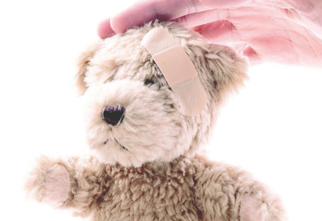 A teddy bear has a bandage on its head