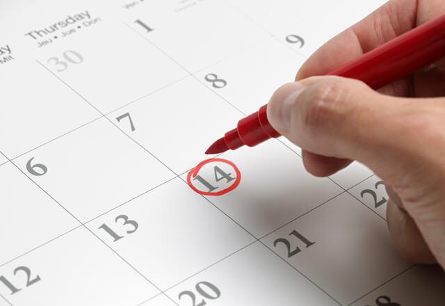 Close up of a hand marking a calendar