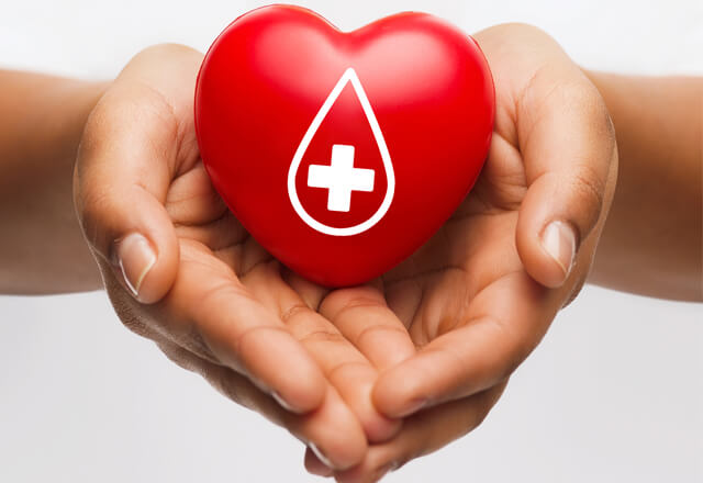 Hands holding a heart with a Red Cross symbol
