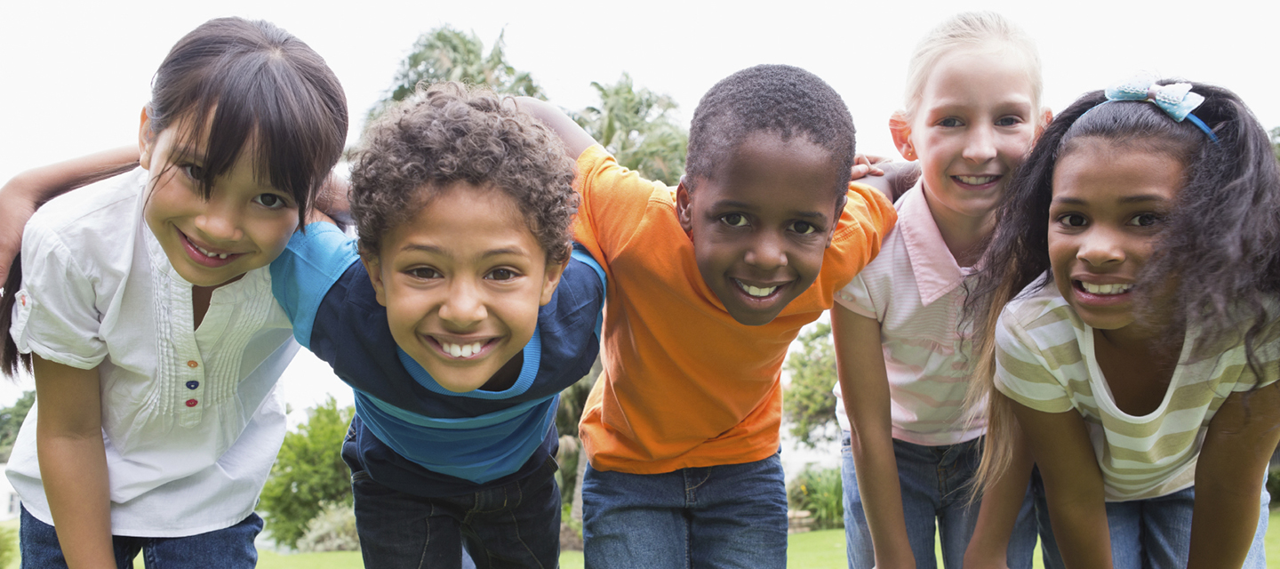Children smile together outdoors.
