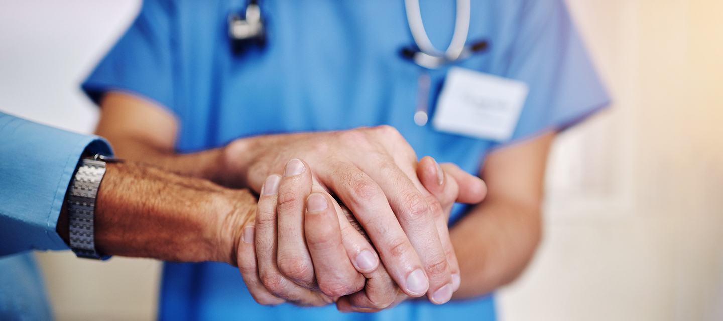 A close-up of a doctor holding a patient's hands.