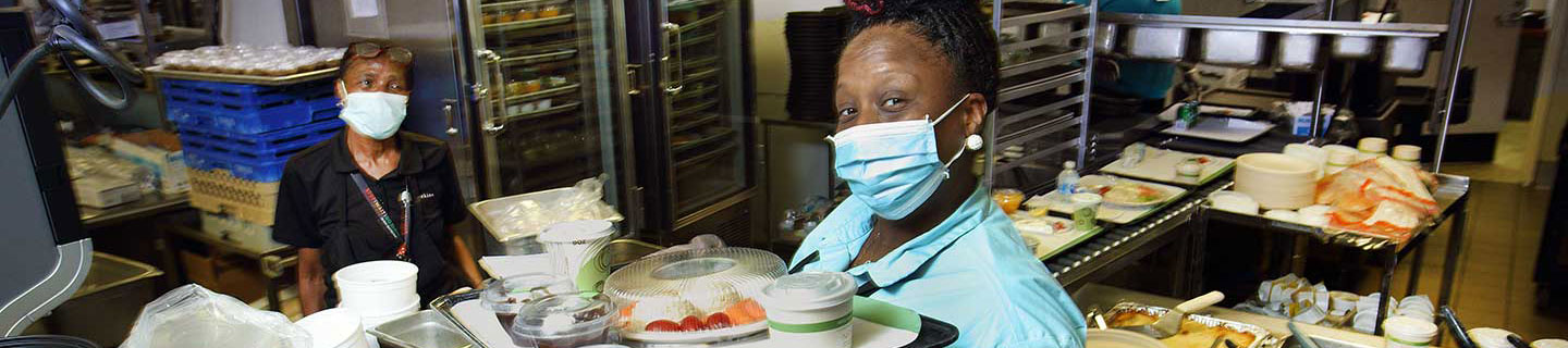 Food service employee wearing a mask and holding a tray of food.