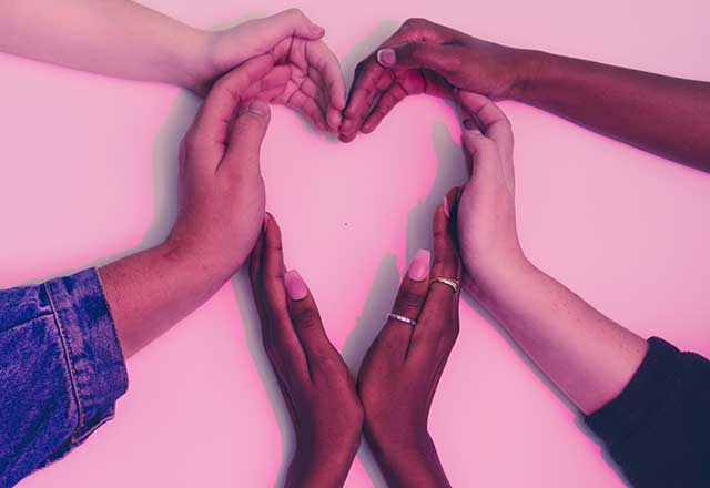 hands forming a heart shape on a pink background