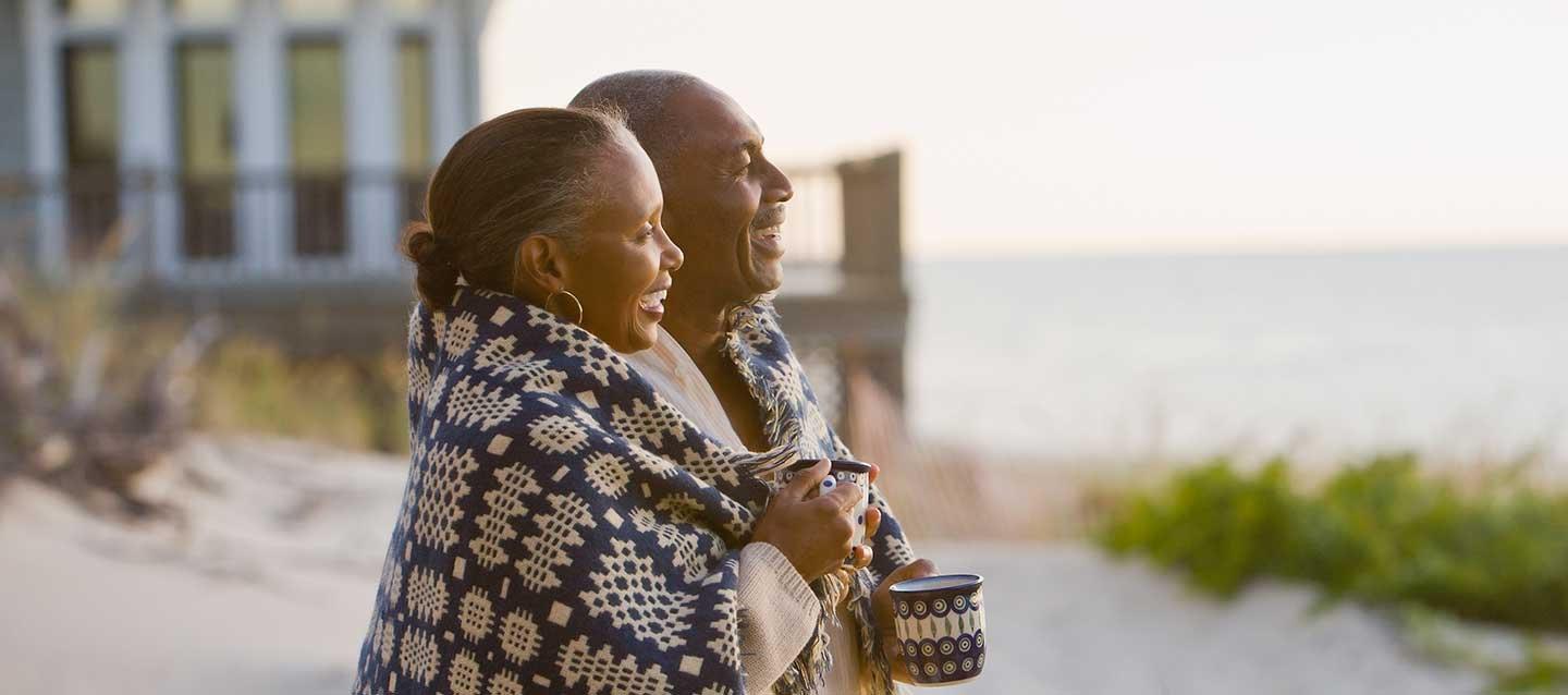 Seniors couple standing by a beach house.