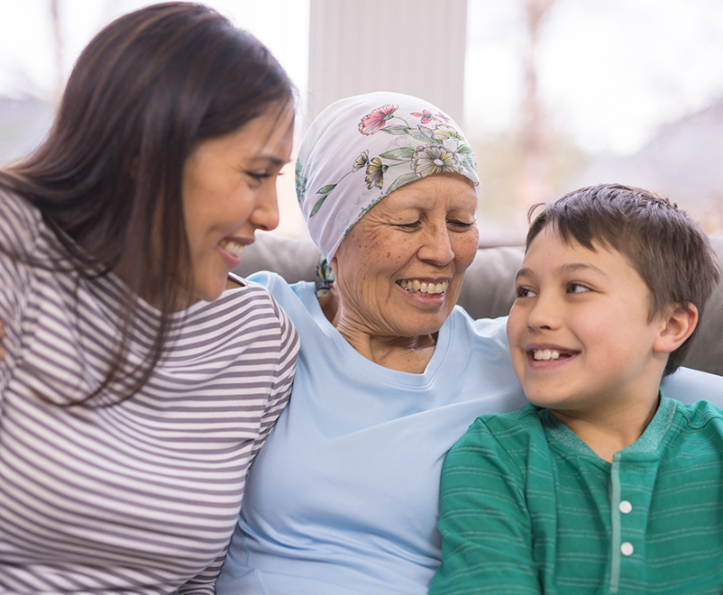 stomach cancer treatment - mature woman wearing scarf with grandchildren